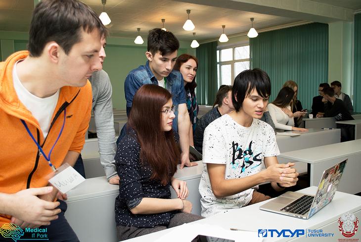 Школьники сидят за партами, на столе – ноутбук