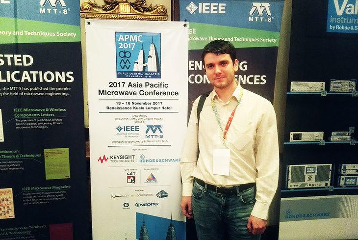 Андрей Коколов на фоне баннера конференции